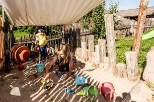 Viele Spielsachen in der Sandkiste mit Sonnenseegel